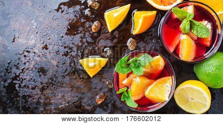 Traditional cold spanish sangria cocktail with red wine and ingredients on a black table, citrus fruit orange lime lemon mint leaves and ice for hot summer days. Top view flat lay overhead, copy space