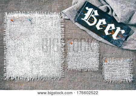 Rectangle pieces of white burlap pinned as various frames on gray burlap background. Wood signboard with text 'Beer' on draped canvas in the corner. Rustic style eco-friendly template