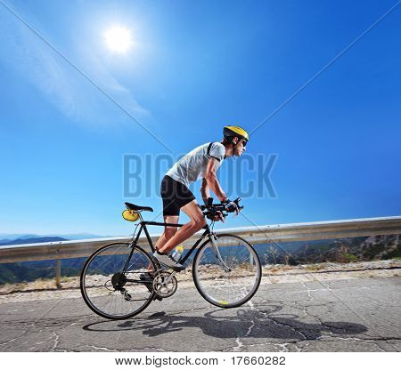 Cyclist riding a bicycle in Macedonia with a sun in the background