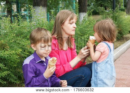 Mother with boy and baby girl sitting in summer park eating icecream