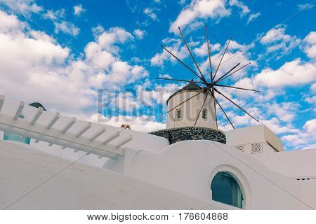 Picturesque white house and windmill in Oia or Ia on the island Santorini, Greece