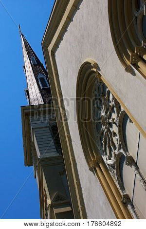 A front street sidewalk perspective of the rosary window and steeple of the Citadel Square Baptist Church in Charleston, SC