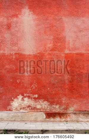 Aged weathered red street wall. Architecture background