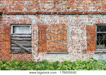 Old red brick wall with some windows and green grass architecture background