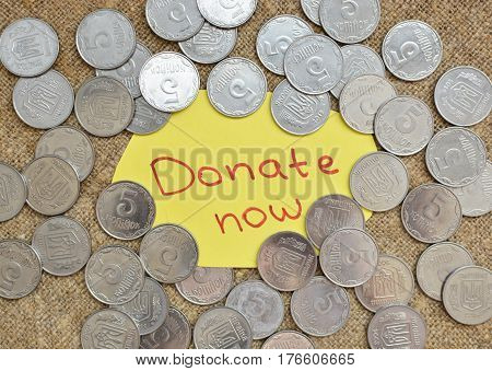 A Lot Of Coins Lying On The Background Of Burlap With A Label With The Words For A Donation Now. Ukr