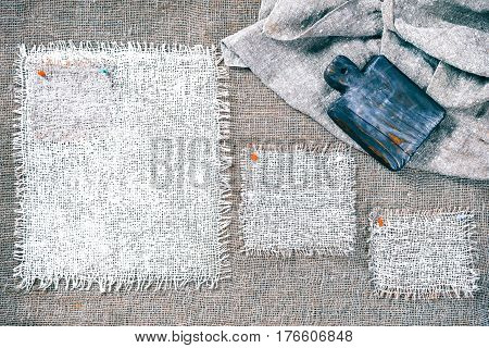 Rectangle pieces of white burlap pinned as various frames on gray burlap background. Wood cutting board on draped canvas in the corner. Rustic style eco-friendly food template