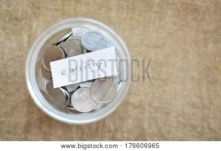 Glass Jar Filled With Coins Labeled With The Words Equity. View From Above. Background Of Burlap. Th