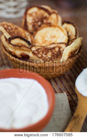 Cooked Homemade Pancakes On A Dining Table In A Wicker Plate Next To Sour Cream For Breakfast. Sweet