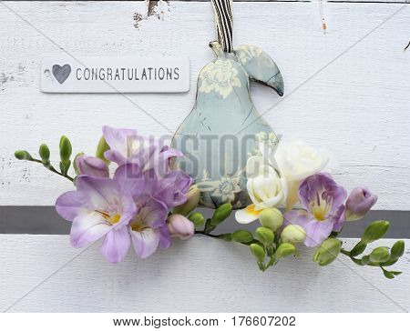 Unusual shabby chic decoration of metal pear and freesias with a congratulations sign