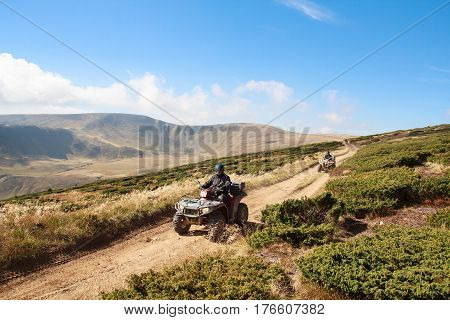 Tourists on quad bikes travel in the mountains. Carpathians