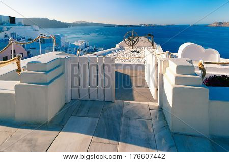 Central tourist street of Oia or Ia with white houses, Aegean Sea and islands in the background, Santorini, Greece