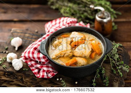 Meat stewed with carrots in sauce and spices in cast iron pan on dark wooden rustic background