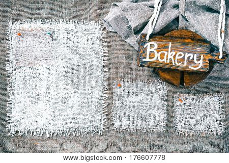 Rectangle pieces of white burlap pinned as various frames on gray burlap background. Wood signboard with text 'Bakery' on draped canvas in the corner. Rustic style eco-friendly template