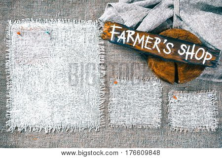 Rectangle pieces of white burlap pinned as various frames on gray burlap background. Wood signboard with text 'Farmers shop' on draped canvas in the corner. Rustic style eco-friendly template