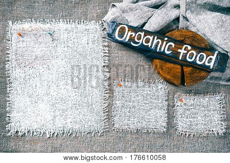 Rectangle pieces of white burlap pinned as various frames on gray burlap background. Wood signboard with text 'Organic food' on draped canvas in the corner. Rustic style eco-friendly template
