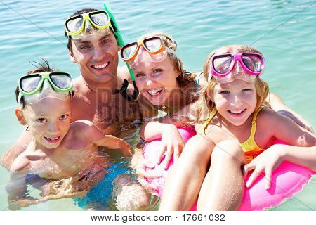 Portrait of cheerful family in aqualungs looking at camera with smiles