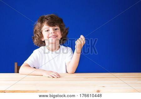 Happy curly cute boy looking at the camera clenched fist. Close-up. Blue background.