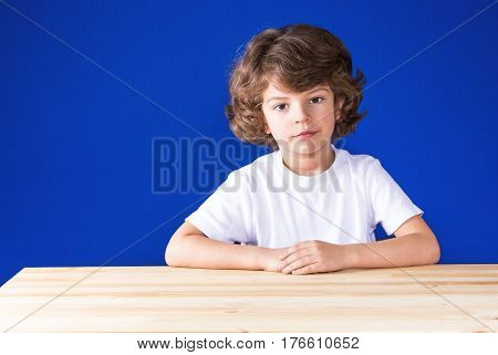 Serious curly cute boy sitting at a wooden table and sadly looks at the camera. Close-up. Blue background.
