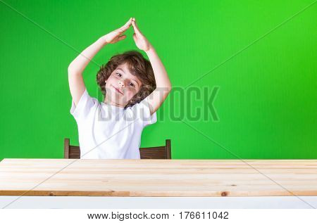 Curly cute boy holding his hands above his head house smiling and looking at the camera. Close-up. Green background.