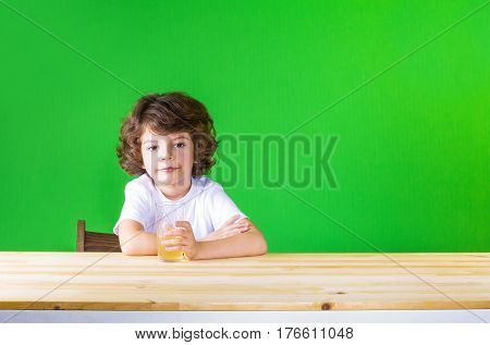 The curly-haired pretty boy holding a glass of juice smiling looks into the camera. Close-up. Green background.