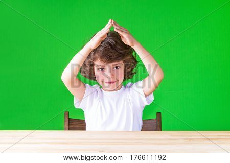 Curly cute boy with hands clasped house looking at the camera over your head. Close-up. Green background.