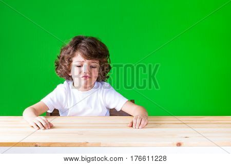 The curly-haired pretty boy sticking out his mouth sitting at a desk crying. Close-up. Green background.
