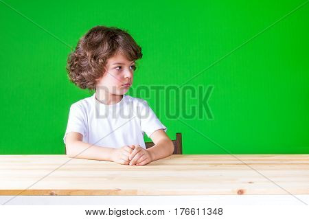 The curly-haired pretty boy looks suspiciously left sitting at the table. Close-up. Green background.