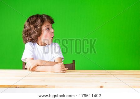 Curly resentful boy sitting half-turned mouth open looking away. Close-up. Green background.