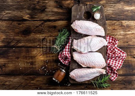 Raw turkey wings on wooden background top view copy space flat lay