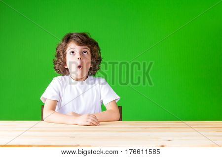 Curly boy stares upward openmouthed. Close-up. Green background.