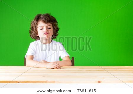 Curly boy sticking out his lips in disbelief looks at the table. Close-up. Green background.