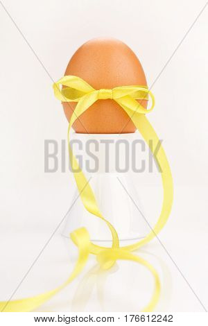 egg with  yelow festive ribbon isolated on white