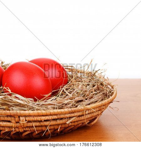 Red Easter eggs in a straw nest isolated