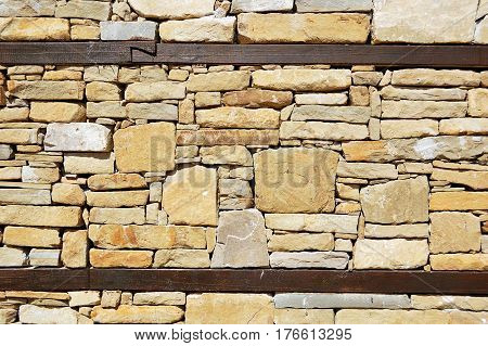Wall of a traditional bulgarian house with wooden beam between layers of stones