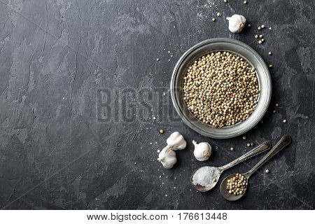 White pepper garlic and salt on dark grey culinary background various spices directly above flat lay copy space