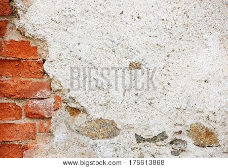 A fragment of a tumbledown plastered brick wall