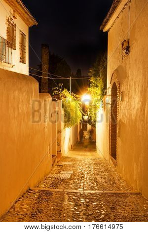Cobblestone narrow street in historic Albacyn district of Granada at night