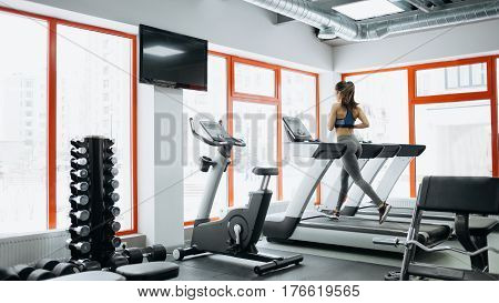 Young Fit Pretty Woman Doing Exercises On The Treadmill