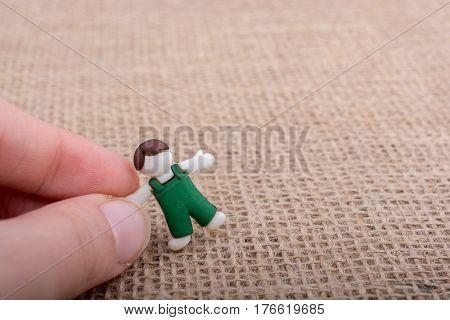 Little Child Figurine In Hand On Brown Backgorund