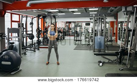 Sporty Woman Standing With Arms Crossed In Fitness Gym.