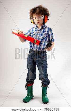 Cute little worker with a level and a walkie talkie. Gray background.