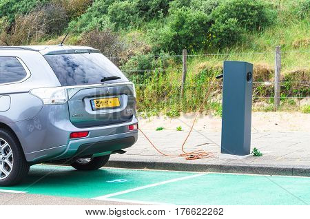 DEN HAAG SCHEVENINGEN THE NETHERLANDS - JUNE 17 2015: Electric car at a charging station on the beach parking in Scheveningen Holland. Seperate parking with charging station for electric vehicles. Vehicles can be connected by cable to the station for rech