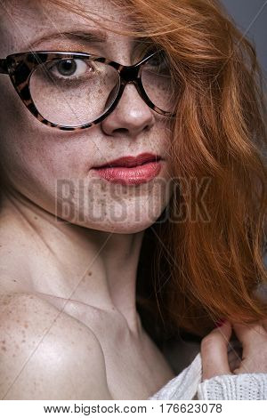 Portrait of a redhead freckled girl in glasses