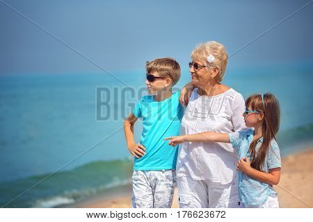 Grandmother with grandchildren having fun together on the seaside
