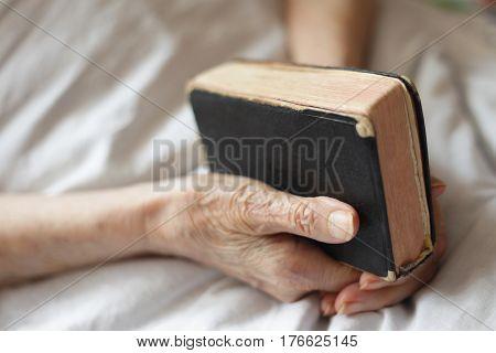 Seniors hands with Bible. Praying to God