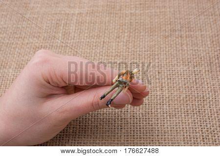 Man Figurine In Hand On Linen Canvas Background