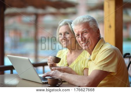 Portrait of an elderly couple with a laptop in a cafe