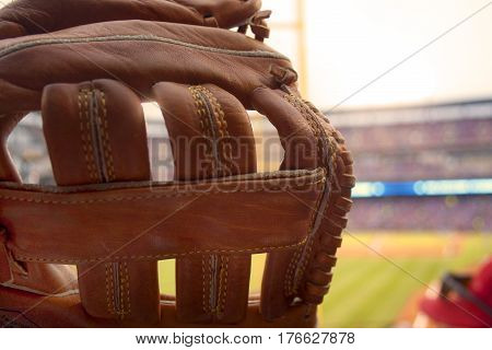 A baseball glove ready to catch a foul ball at a baseball game.
