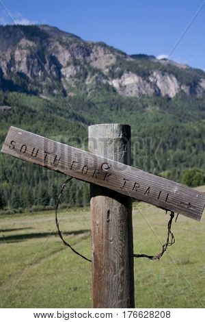 Wooden hiking trail sign for South Forth Trail in Colorado mountains.