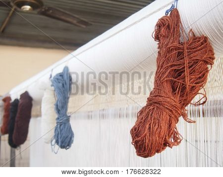 Skeins of natural dyed yarn hanging on a loom.